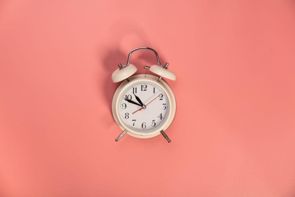 Réveil blanc sur fond rose